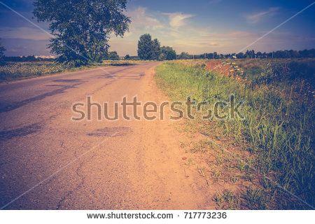 Old cracked, damaged asphalt road in countryside at sunny day, vintage background.