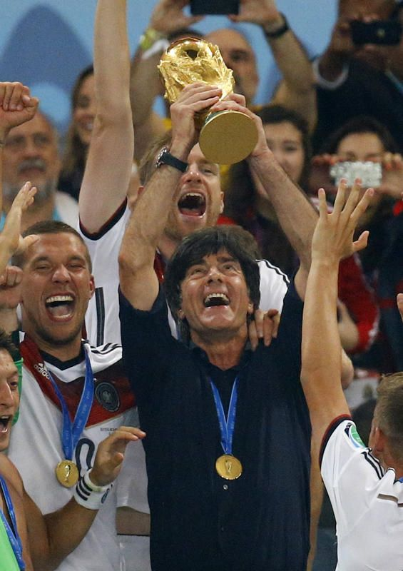 Germany's coach Joachim Loew lifts the World Cup trophy next to Lukas Podolski (L) after the 2014 World Cup final between Germany and Argentina at the Maracana stadium in Rio de Janeiro July 13, 2014. REUTERS/Kai Pfaffenbach