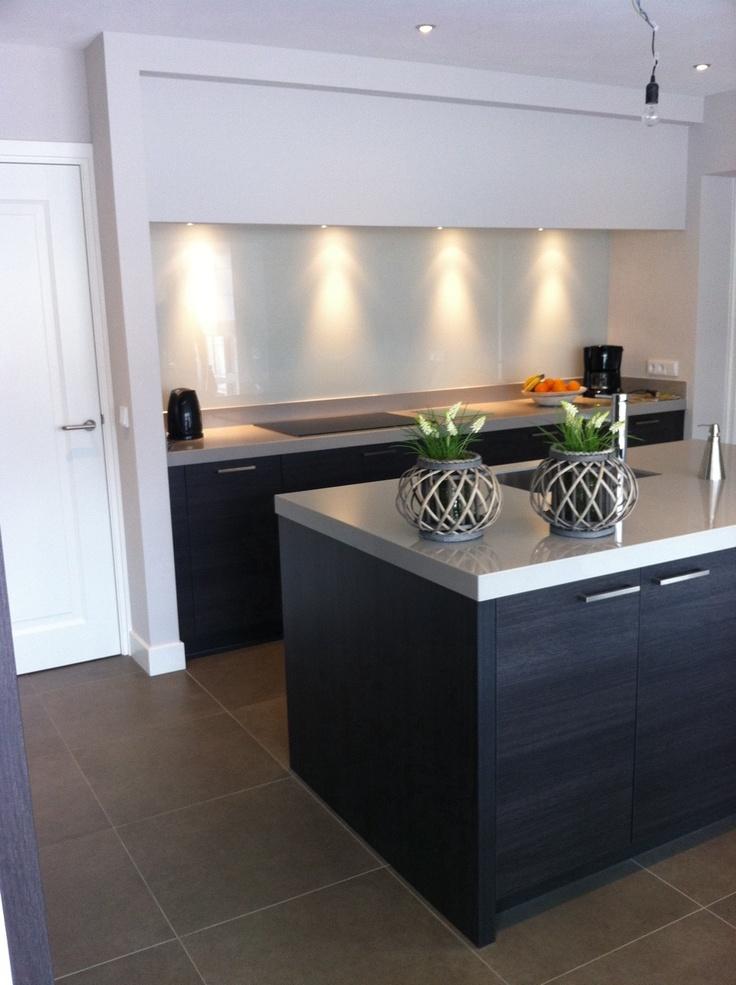 Donker eiken keuken met spoeleiland en kooknis met bouwkundig vormgegeven afzuigschouw — bij Sterksel.