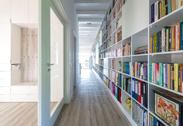La libreria su disegno di Foldes Architects, realizzata in legno bianco trattato e dipinto di bianco, sconfina nel corridoio, con parquet in rovere. Una porta a vetri conduce al guardaroba e alla zona notte
