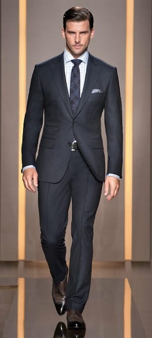 A perfectly tailored Men's suit in dark or charcoal gray. The booties appear to be spectators though it could be the way the light is cast on them.