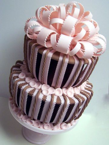 "Captiva Cake Pink and Brown - This is my own signature design -- fustrated with disaster whimsy cakes, but wanting a differnt look -- developed the Captiva line == Captiva, French for ""cage"" -- these cakes are encased in a cage of fondant -- made basically by putting covered boards that are at least 2 inches larger than the cake -- and then applying fondant strips  --     This is one of my favoirtes...     the create a great illusion --"