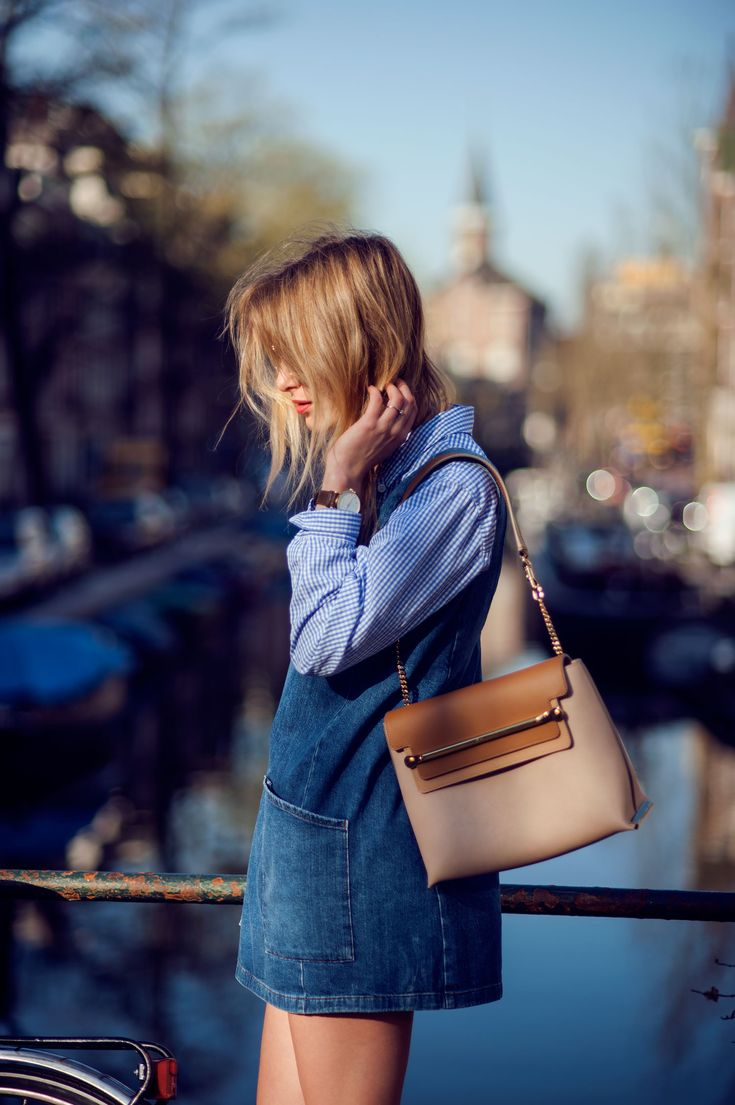 Rebecca Laurey is wearing a 70′s denim dress over TopShop, over a pale blue and white striped shirt and the bag is from Chloe