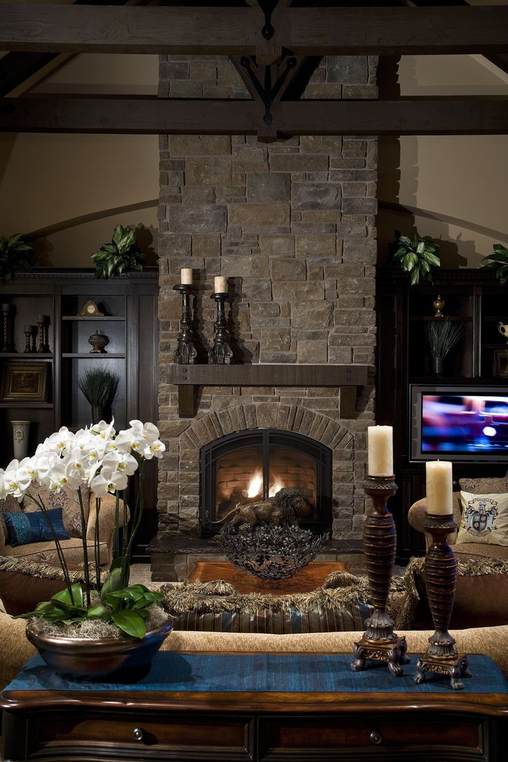 Home theaters are what you make it and this homeowner went with the traditional living room setting featuring a stone fireplace, open shelves and wood beams above.