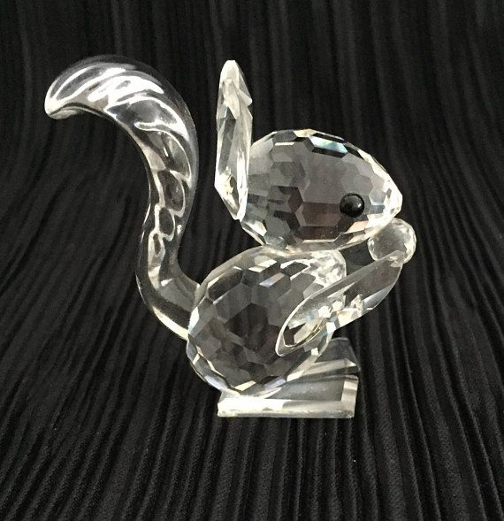 A beautiful Swarovski Silver Crystal Squirrel with long ears, holding a nut. Complete with box and certificate. From the Woodland Friends Collection. Based on a Red Squirrel. No: 001871. Designed by Max Schreck Piece now retired. Apx height 4.5cm, width 2cm, depth 4cm.  This lovely