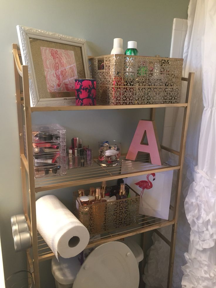 Kate spade inspired bathroom organization/ Lilly Pulitzer bathroom/ pink and gold bathroom decor / bathroom organization/ small bathroom/ small space organization/ bathroom racks/ apartment bathroom storage/   Bathroom rack from Home Depot spray painted gold. Lilly prints, gold spray painted metal baskets, hobby lobby painted letter.