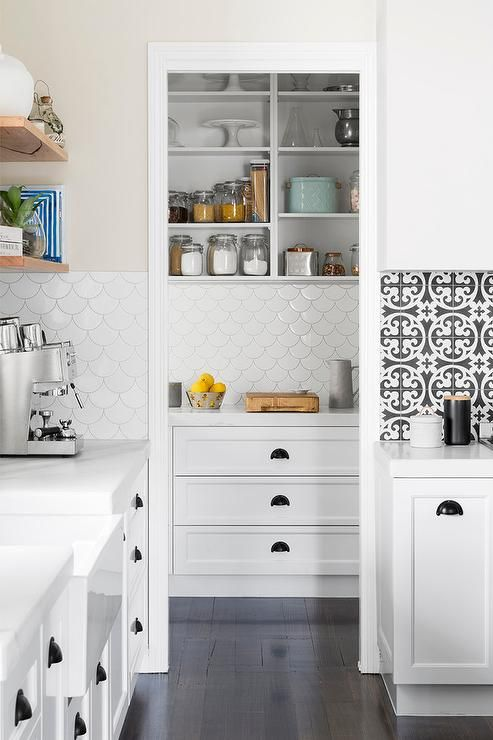Ebony wood floor panels lead to a white pantry fitted with white open shelves fixed above white cabinets donning oil rubbed bronze hardware and a honed white marble countertop complementing Tabarka Studio Artisan Terracotta Fan Tiles.