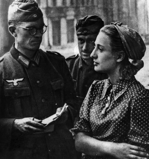 Russian woman stares straight ahead, refusing to answer a German soldier, 1941