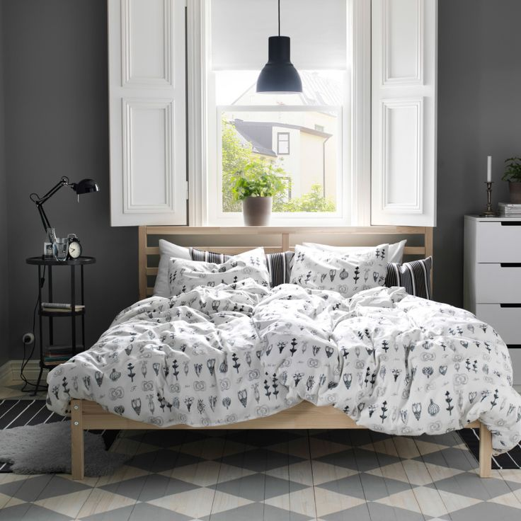Indoor shutters.   A rustic bedroom with a FJELLSE bed in untreated wood, SÖTVÄPPLING graphic quilt cover in white and black and GUNNERN pedestal table