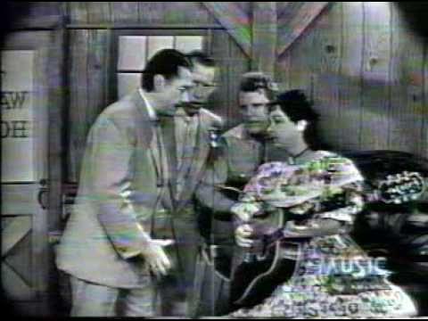 "Wilma Lee and Stoney Cooper with Porter Wagoner - ""Walking My Lord Up Calvary's Hill."" The film is in poor condition, but they sure have that intense, old-time country sound. ""The birds stopped their singing."" What a great detail!"