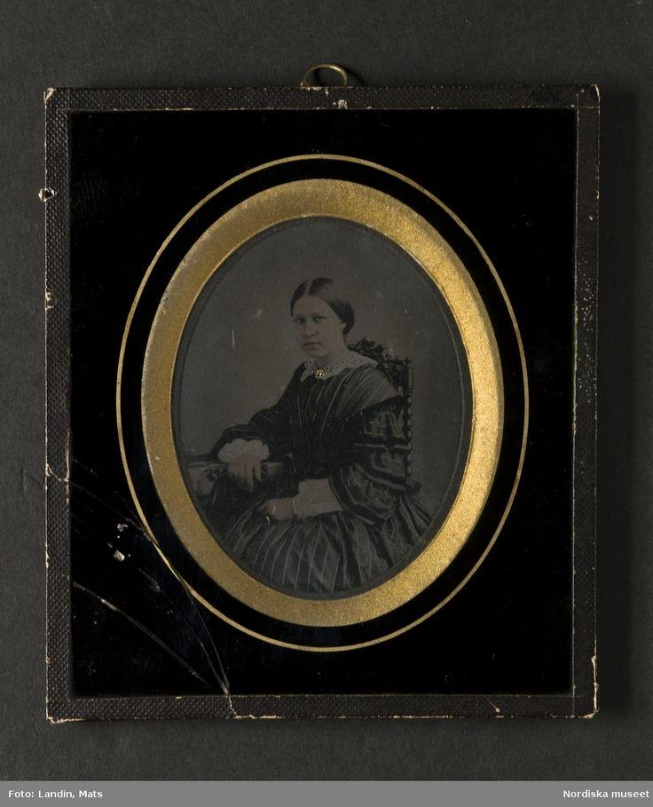 """Porträtt, höftbild, av ung kvinna. Bilden föreställer fru Augusta Flack, född Frestadius (1832-1912). Sitter i stol med högt ryggstycke, klädd i mörkrandig klänning med vida ärmar och volanger samt vit krage. Mittbenat uppsatt hår. Brosch och ring förgyllda. Ambrotyp i glasad ram. På bakstycket påklistrad vit etikett med svart tryckt text: """"W.A. Eurenius & P.L. Quist/FOTOGRAFISK ATELIER/Stockholm/Regeringsgatan No 14"""". Med bläck årtalet """"1858"""". Nordiska museet inv.nr 117638"""