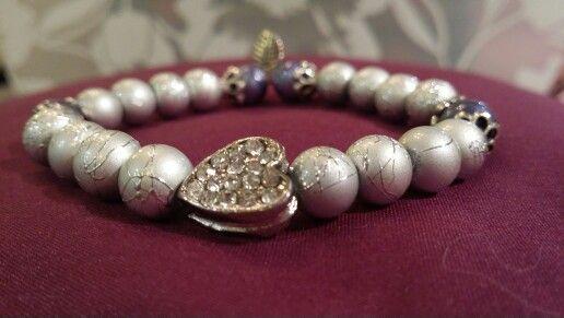 Armband med strasshjärta. Ljust grå pärlor med mönster. Trädda på elastisk tråd. Pris 150 kr inkl frakt.