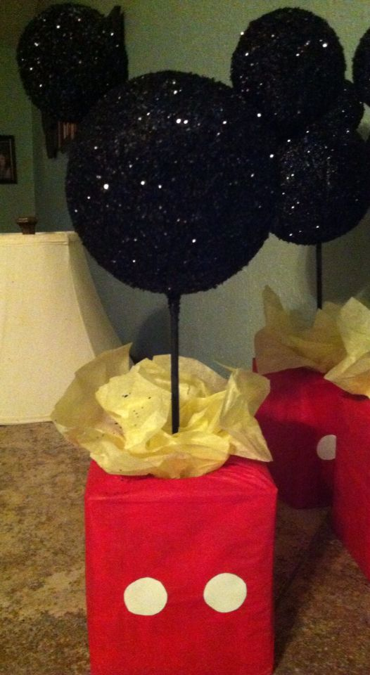 Just finished making these Mickey Mouse centerpieces for my sons 2nd birthday.I used tissue boxes,tissue paper,wooden sticks, styrofoam balls (2 sizes), spray glue,black glitter and paint.To weigh them down I filled the tissue boxes half way with pebbles I had in my backyard.Simple,easy and super cute!