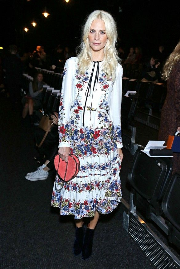 Poppy Delevingne wears a floral midi dress with boots and a heart-shaped pink clutch: