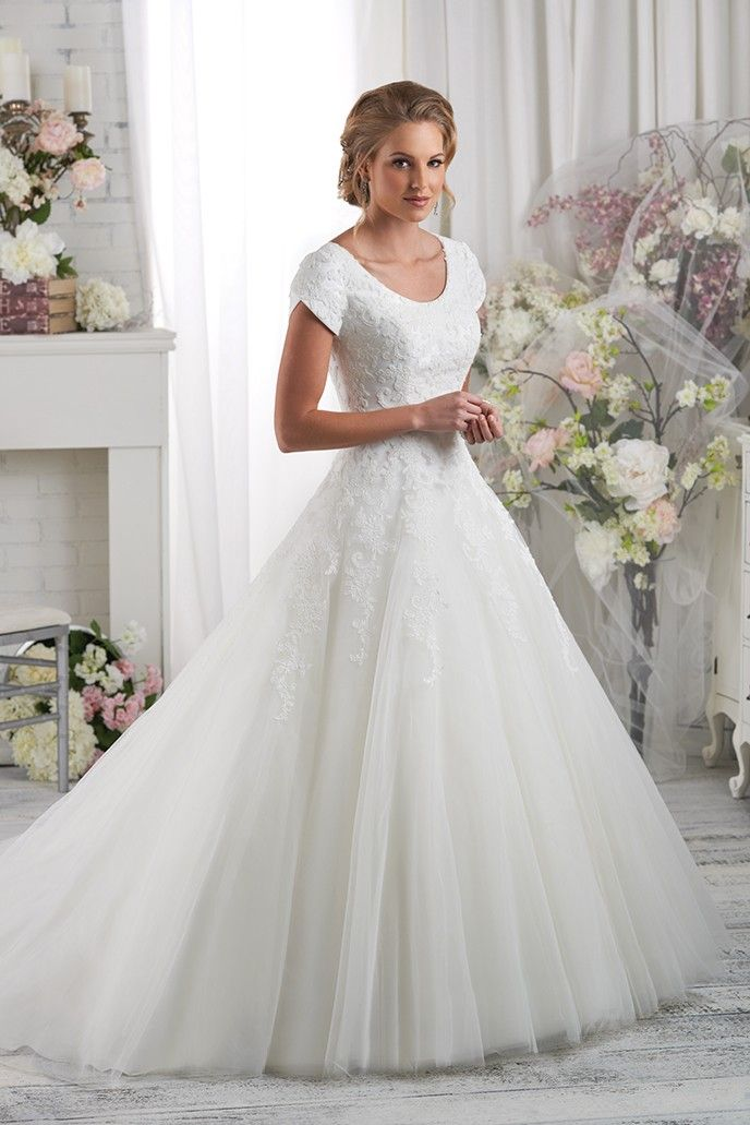 Floral lace details the magnificent modest bodice of this ball gown. The lace then falls softly onto the circular cut skirt and train.  See store for availability and pricing.
