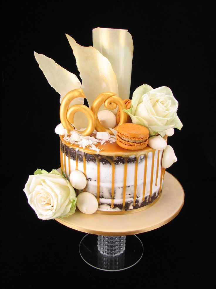 Chocolate mudcake with white buttercream in a semi naked finish. It is decorated with a salted caramel drip and topped with salted caramel macarons, meringue kisses, white chocolate shavings and white chocolate sails with gold dust. I've also added a gold fondant 60 and fresh white roses.