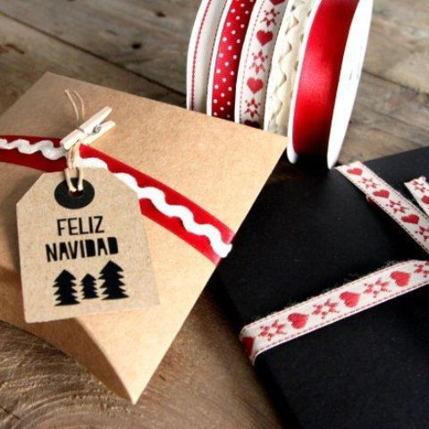 Decoracion de regalos de navidad con tiras rojas y blancas y etiqueta