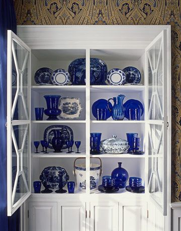 The arrangement of cobalt glass, transferware, and Chinese porcelain in the dining room cabinet reveals Sanders's knack for display. Joshua McHugh  - HouseBeautiful.com