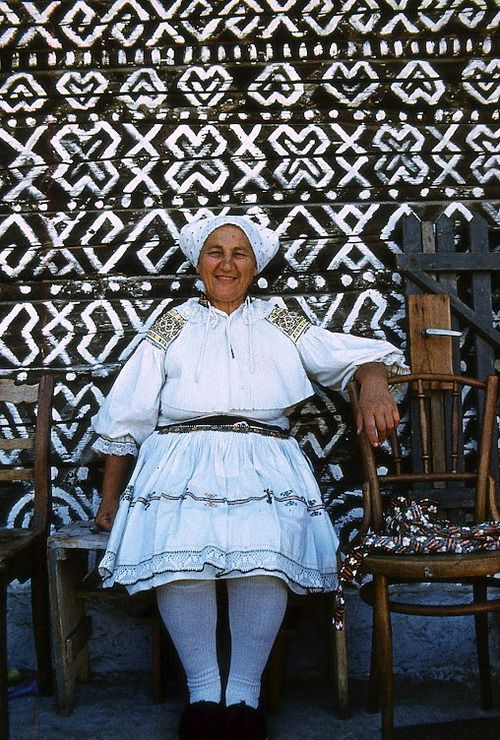 Village woman from the painted town ofČičmany, Slovakia.  The houses in the town all share the same designs and symbols painted on them with lime as the patterns embroidered into local folk costumes. But exactly why the natives decided to ornament their homes in this manner is a mystery.