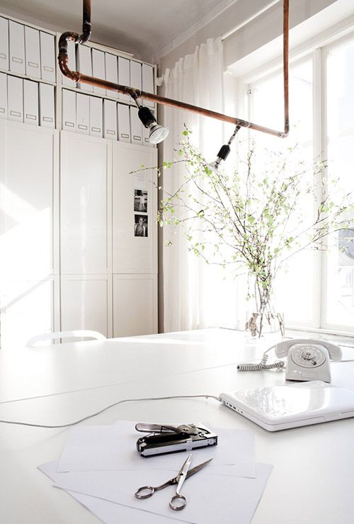 all white workspace.  that copper lighting fixture is so awesome