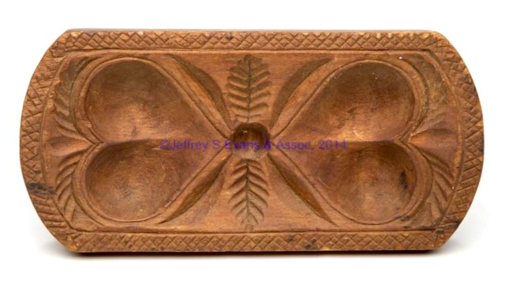 """Jeffrey Evans 11/15/14 Lot# 808.  Description:MID-ATLANTIC CARVED TREEN BUTTER PRINT, rectangular form with curved ends, double hearts with feathered branch between and at each end, within a cross-hatched edge border, friction-fit short baluster-form handle, original dry surface. 19th century. 4 1/4"""" H, 3 1/4"""" x 6 1/2"""".  Very good condition with expected wear. Provenance: From the collection of Marion and Carleton Cotting, Vienna, VA. Estimate: $80 - $120. Realized $2070 hammer, $2380 with…"""