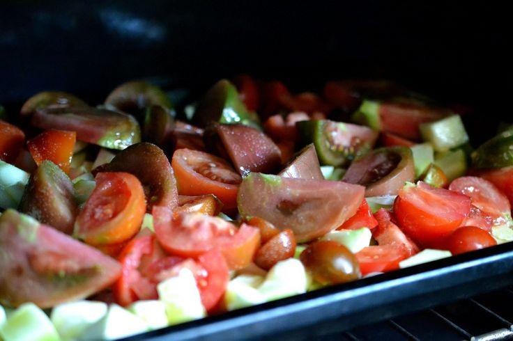 Tomater och andra grönsaker på en plåt i ugnen.