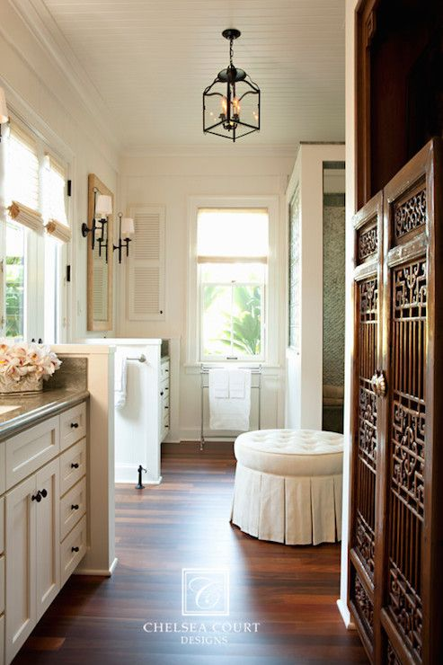 Stunning bathroom features white beadboard ceiling accented with iron lantern over white round tufted skirted ottoman placed in front of French doors dressed in roller shades flanked by his and her washstands accented with oil-rubbed bronze knobs topped with grey countertops. Carved wood doors lead to water closet across from large spa like shower next to freestanding towel warmer.