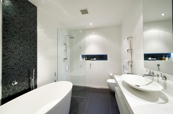 This is quite a small bathroom but you wouldn't know that with how this is pulled off. Walk in shower finished right with gully drain for good water drainage. Free-standing bath, wall hung toilet pan, wall-hung vanity. We especially like the black feature tile behind the bath and inside the shower recess.