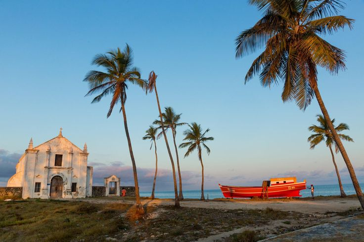 A newly built boat gets a coat of paint near the Church of San Antonio on the Island of Mozambique.