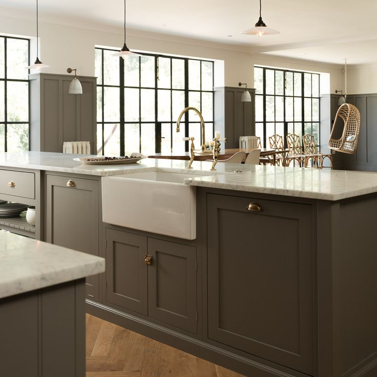 The island in this Queens Park shaker kitchen by deVOL houses a dishwasher, double bin and sink with our Perrin & Rowe 'Ionian' taps