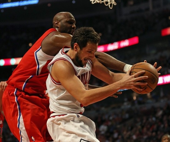 Marco Belinelli of the Chicago Bulls grabs a rebound under pressure from Lamar Odom of the Los Angeles Clippers on December 11, 2012 in Chicago