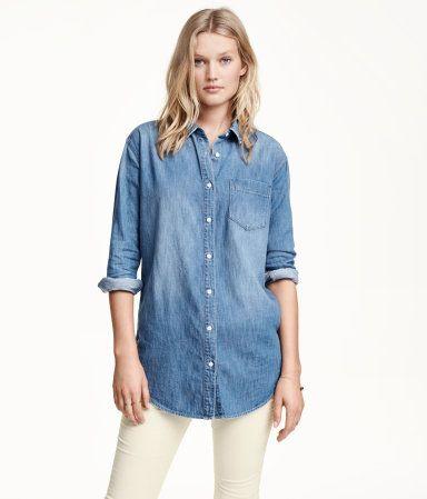 Een lange, oversized overhemdblouse van gewassen denim met slijtagedetails. De blouse heeft een rechte pasvorm, iets verlaagde schoudernaden, lange mouwen en een borstzak. Afgerond aan de onderkant.