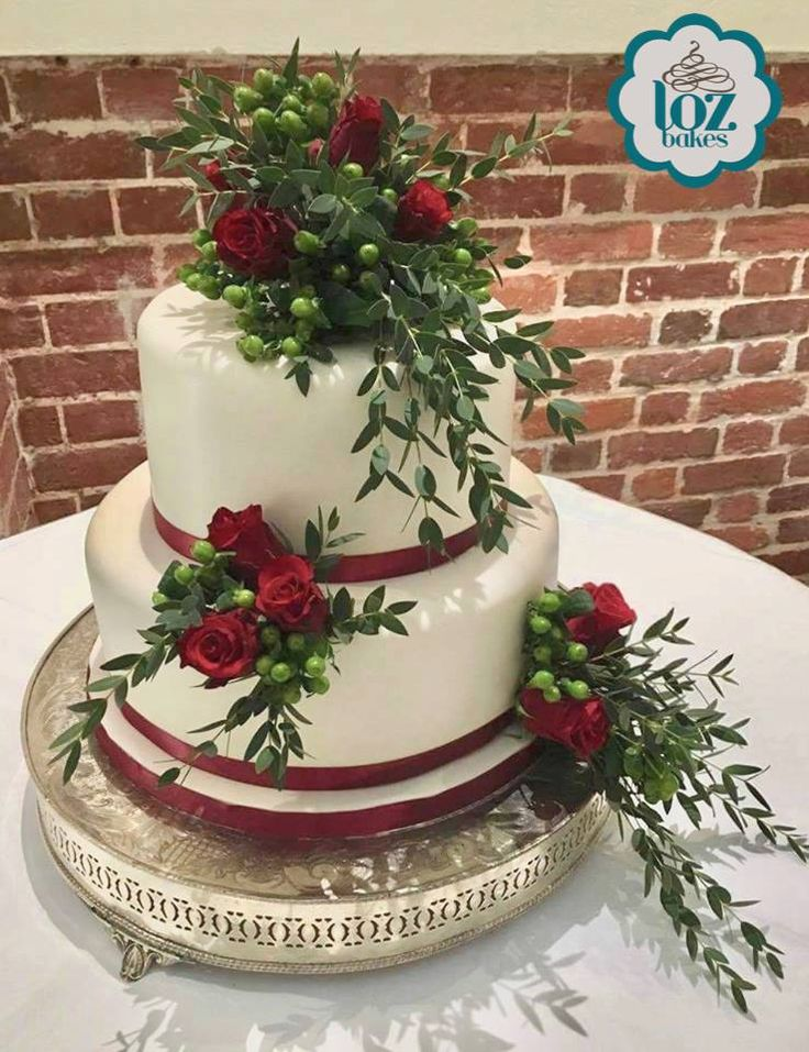 Simple, ivory wedding cake decorated beautifully with real flowers.