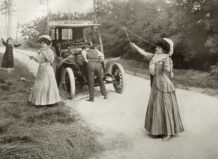 1900 Women playing some kind of string game while the men are fixing the car
