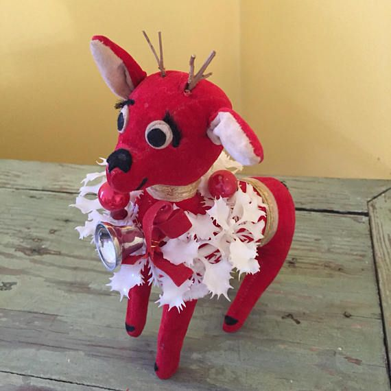 "Standing about 7"" to top of antlers, this cute little guys was loved enough that someone replaced his antlers with little twigs. His body is red velvet and he has a wreath of white plastic Holly around his neck with silver bells. He also has fuzzy eyelashes. R. Dakin Dream Dolls label"