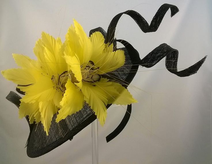 Black sinamay disc mounted on a hairband with yellow feather spray