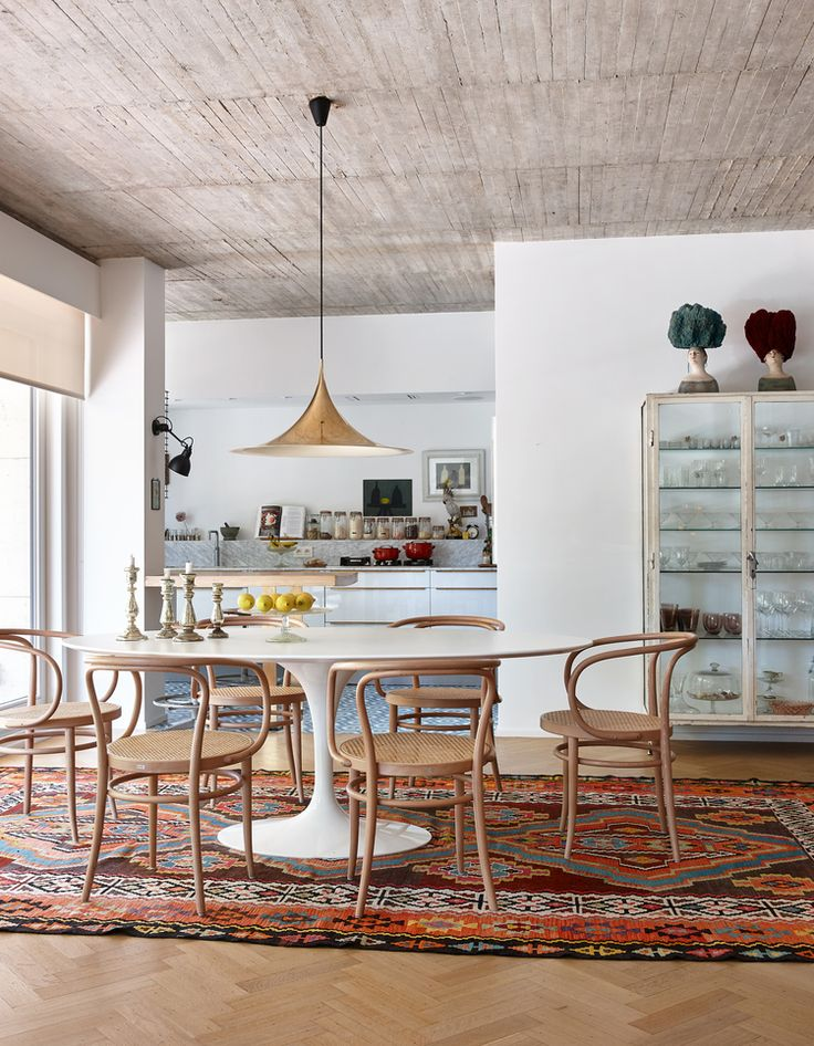 Thonet chairs, Saarinen table, and brass Gubi Semi pendant light in the dining…
