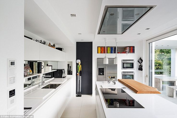 Modern: This German kitchen mixes a white colour scheme with splashes of colour in room's accessories (cost of project not available)