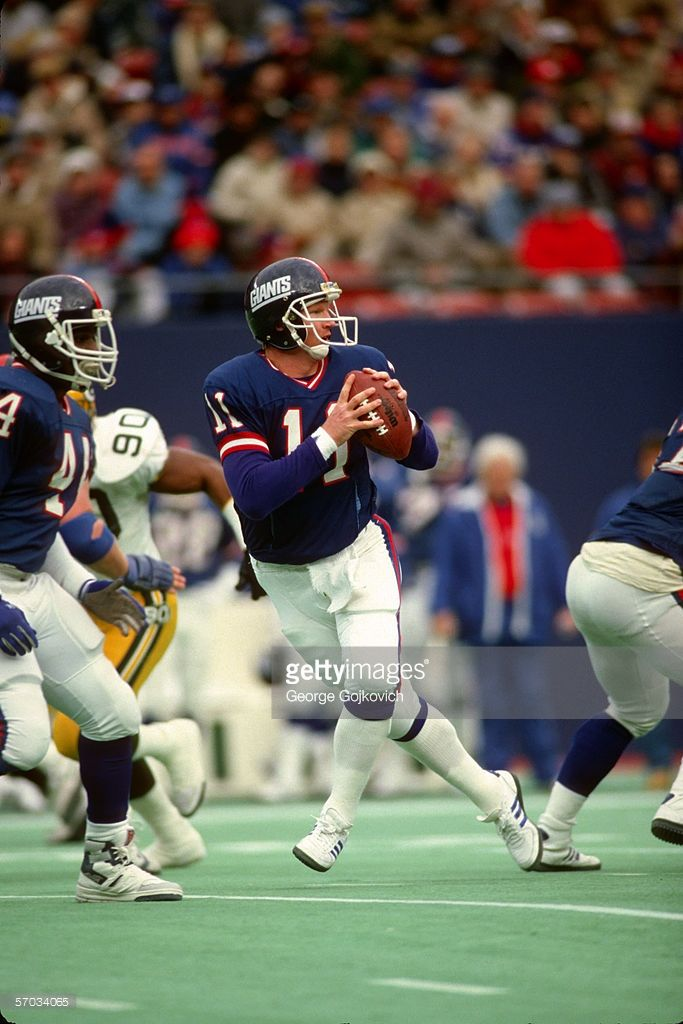 Quarterback Phil Simms #11 of the New York Giants drops back to pass against the Green Bay Packers at Giants Stadium circa 1985 in East Rutherford, New Jersey.