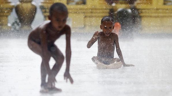 Meninos brincam na chuva em monastério budista utilizado como abrigo para vítimas da violência em Sittwe, em Mianmar