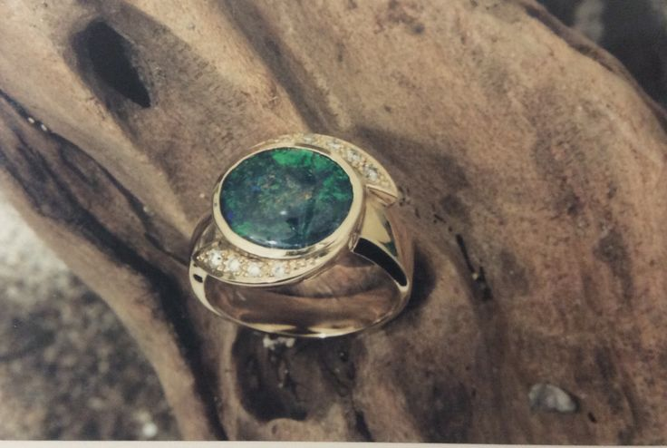 Opal ring with a spiral frame of diamonds on a wide band  in yellow gold