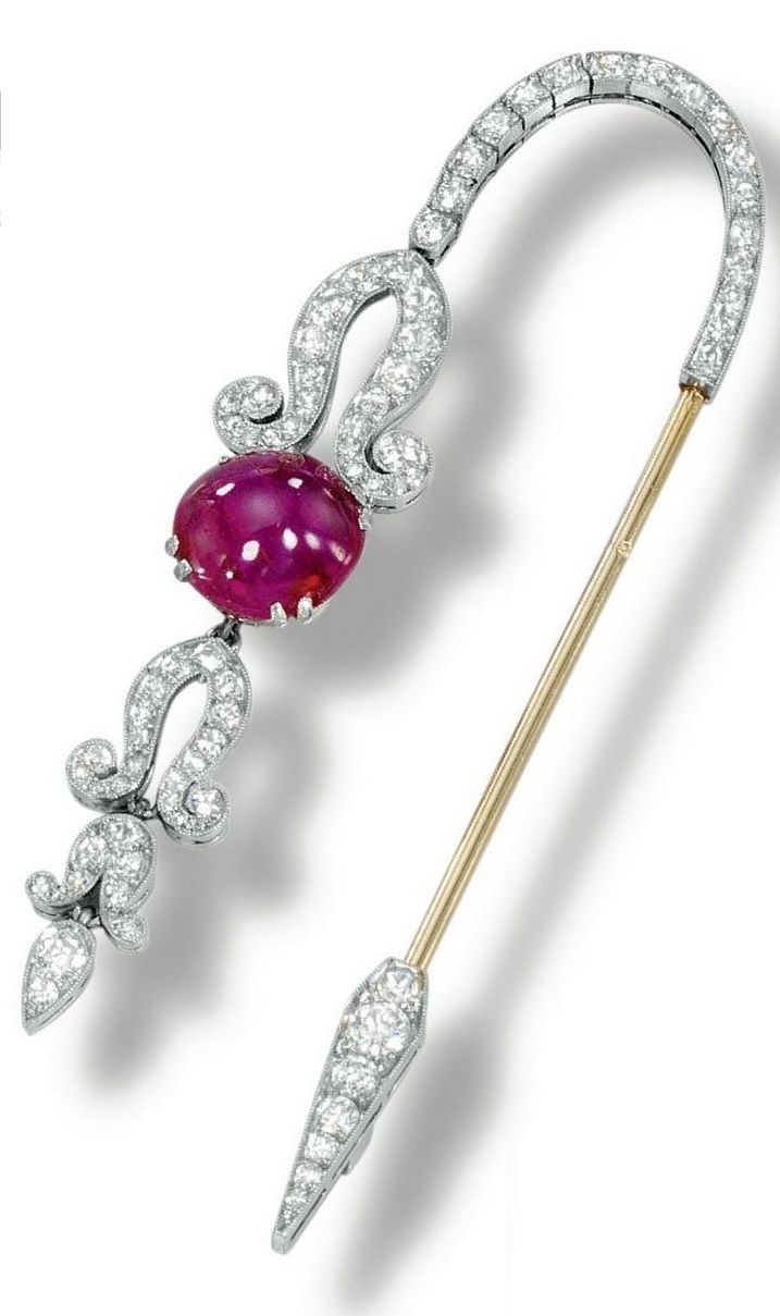 An Art Deco ruby and diamond jabot pin, Janesich, 1920s. Designed as single- and circular-cut diamond cascade motif set with a cabochon ruby, mounted in platinum, signed Janesich and numbered, French assay and maker's marks. #Janesich #ArtDeco #JabotPin