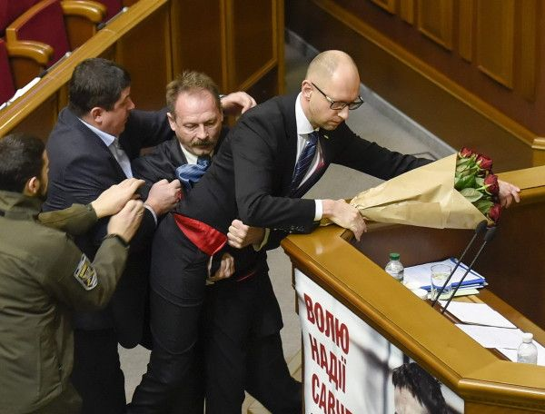 Ein Abgeordneter der Rada reißt am Freitag den Premier Arseni Jazenjuk vom Podium des Parlaments in Kiew. (Foto: dpa)
