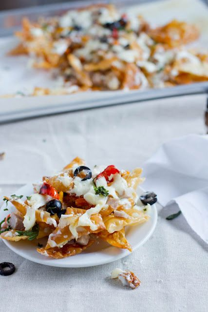 Italian Nachos. Fried Wontons, smothered in creamy Alfredo Sauce, Mozzarella Cheese, Chicken, sautéed Peppers, Olives, and Parsley. Nacho lovers are sure to love this recipe! ohsweetbasil.com