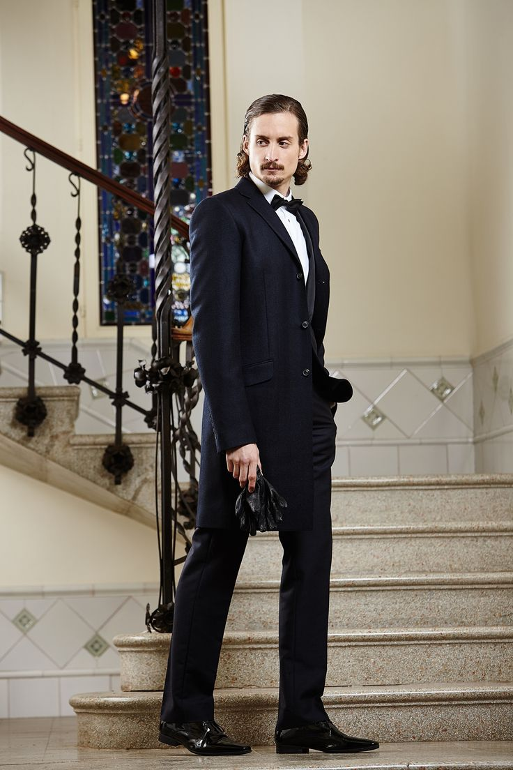 Men's long black tailored jacket with classic black tailored trousers and a crisp white shirt.