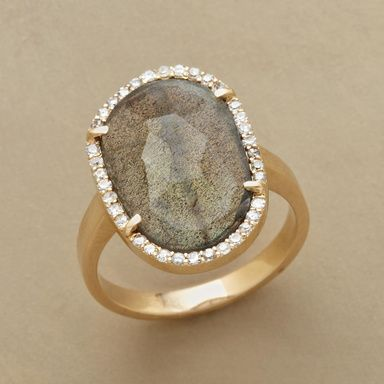 LAVISH LABRADORITE RING--Gleaming diamonds rim the irregular border of a faceted slice of labradorite, an opulent combination set in 14kt gold. Each ring is unique. Stone size and shape will vary. Whole sizes 5 to 9. Note: This ring is running slightly large, please size down to the next full size for half sizes.