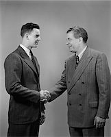 1940s - 1950s TWO BUSINESS MEN OF DIFFERENT GENERATIONS SHAKING HANDS