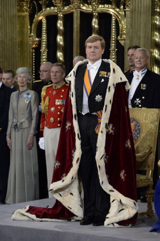 HM King Willem Alexander of the Netherlands stands as HM Queen Maxima of the Netherlands sits in front of members of the royal household during their inauguration ceremony at New Church on 30 April 2013 in Amsterdam