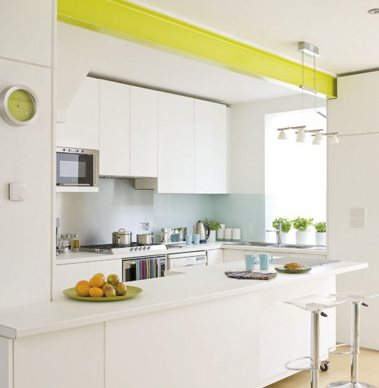 Here, an all-white kitchen has been given interest by painting the overhead steel beam in a zingy lime colour. The pale-blue splashback is made with spray-painted glass and is a popular and practical choice for modern kitchens. Kitchen units IKEA