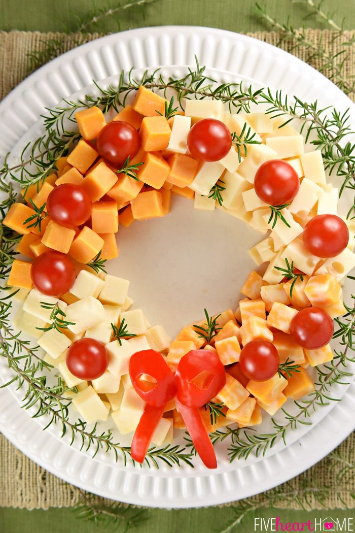 Holiday Cheese Wreath. Made by arranging cubes of cheese in a ring, accenting with cherry tomatoes and a garland of rosemary, and finishing off with a bell pepper bow!
